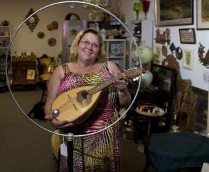 Kim Wichowski shows a Russian stringed instrument at her antique store in Barrington. / Jose F. Moreno/Courier-Post